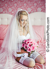 Beautiful young bride underwear sitting on a bed with a bouquet of flowers in hands and with a veil on her head. Morning the bride.