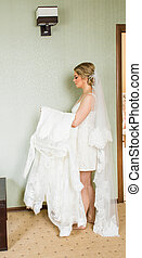 Beautiful young bride with a white  dress. Last preparations for the wedding.