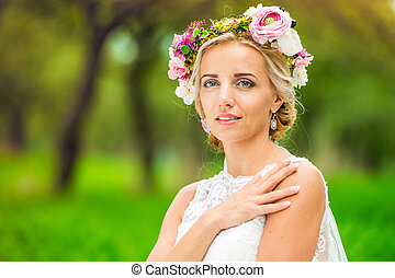 Beautiful young bride with flower wreath outside in nature