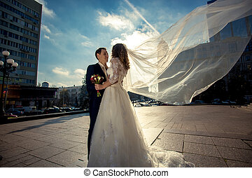 bride with long veil hugging with groom on street at windy day