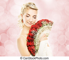 Beautiful young bride with luxury bouquet of red roses.