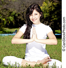Beautiful young brunet yoga girl on green grass in park.