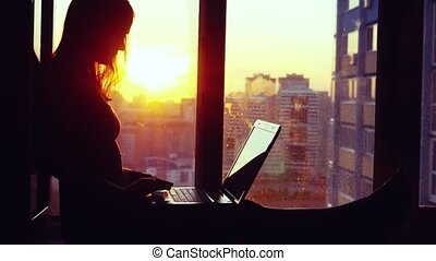 Beautiful young brunette business woman working on her laptop during sunset. Girl sitting on the window at modern building blurred background in city