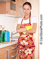 Beautiful young brunette cleaning kitchen. serious girl standing in apron and folded hands
