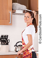 Beautiful young brunette cleaning the kitchen. attractive girl standing in apron and using duster