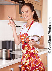 Beautiful young brunette cooking food. housewife smiling in kitchen and tasting meal