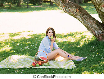 Beautiful, young brunette eating an apple in the park