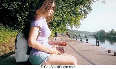 Beautiful young brunette eating sweet cherries on city park embankment
