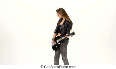 Beautiful young brunette girl with the electric guitar on a white background. Slow motion.