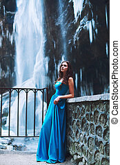 Beautiful young brunette in a blue dress on a background of a glacier and a mountain massif