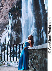 Beautiful young brunette in a blue dress on a background of a mountain massif and a glacier