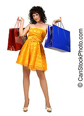 brunette in a yellow dress with shopping bags over white