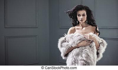 Beautiful young brunette lady wearing stylish fur coat