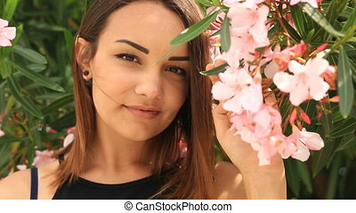Beautiful young brunette smiling cute and looking at the camera on a background of pink blossoming tree flowers
