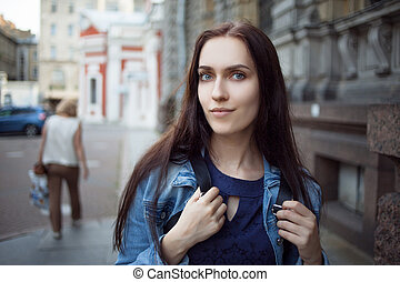 Beautiful young brunette with a backpack in the city