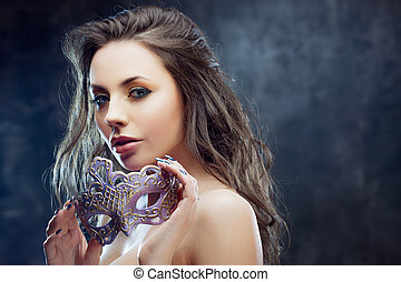 Beautiful young brunette with a purple mask in her hands. Carnival, celebration