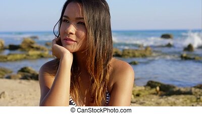 Beautiful young brunette woman at the beach