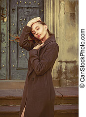 Beautiful young brunette woman in a grey coat