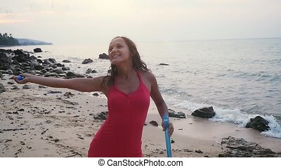 Beautiful young brunette woman playing with soap bubbles on tropical beach at sunset time. slow motion.
