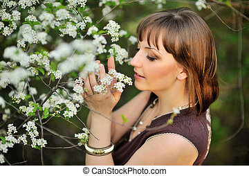 beautiful young brunette woman standing near tree