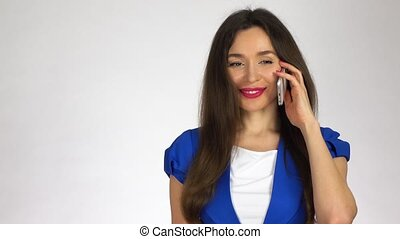 Beautiful young brunette woman talking on her cell phone against white background. 4K clip