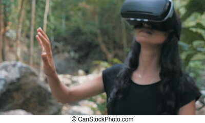 beautiful young brunette woman uses virtual reality glasses in the jungle