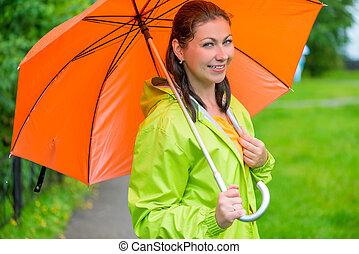 beautiful young brunette woman with an orange umbrella closeup