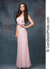 Beautiful young brunette woman with her hair posing in a i long pink dress. Studio, on gray background