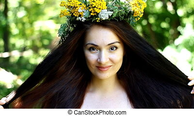 Beautiful young brunette woman with long hair and wreath of flowers