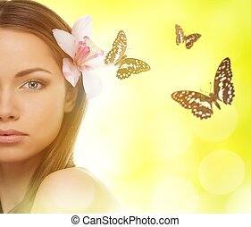 Beautiful young brunette woman with orchid flower in her hair and butterflies