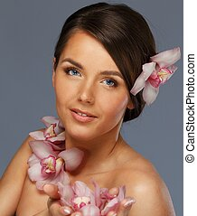Beautiful  young brunette woman with orchid flowers