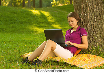 Beautiful young brunette working on a laptop in the park