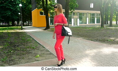 beautiful young business girl in red suit and sunglasses walks down the street on high heels