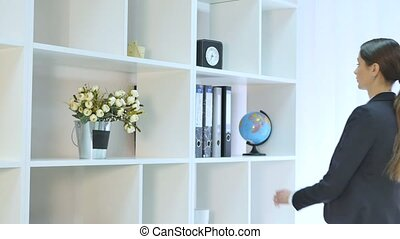 beautiful young business woman holding folder in bright office at office