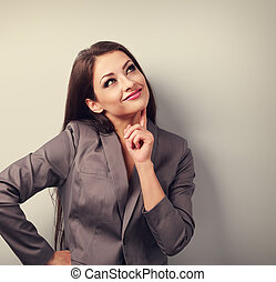 Beautiful young business woman in suit thinking and looking up. Toned portrait with empty space