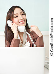 Beautiful young business woman sitting at her desk , speaking on the telephone