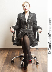 Beautiful young business woman sitting on a chair