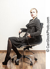 Beautiful young business woman sitting on a chair in office