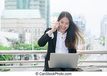 Beautiful young business woman smiling working with laptop out door, looking screen With gesture of happy rejoicing, shock, surprise emotion
