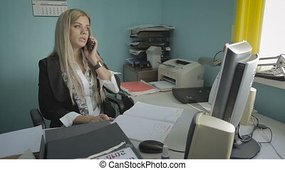 Beautiful young business woman talking on phone in office stock footage video
