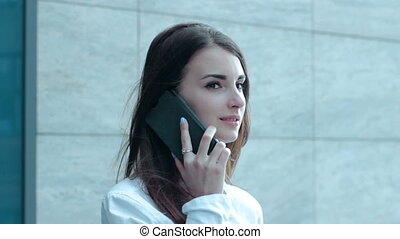 young business woman talking on the phone on the street