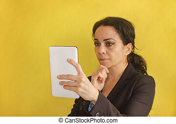 Beautiful young business woman, with pigtail, black jacket, isolated on a background, looking at her tablet