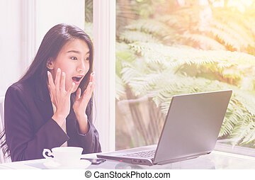 Beautiful young business woman working with laptop ,looking screen With gesture of rejoicing, shock, surprise emotion