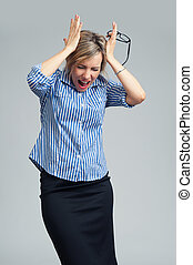 businesswoman screaming and holding head in hands -...
