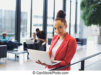 Beautiful young businesswoman with laptop in modern office