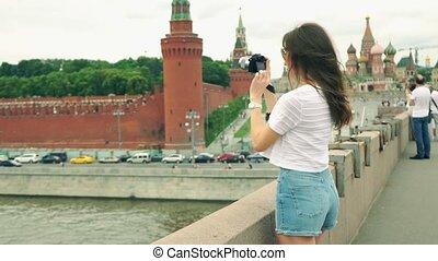 Beautiful young caucasian brunette girl taking photos of Moscow Kremlin