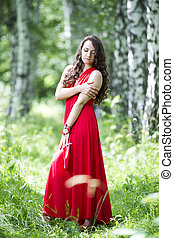 Beautiful young caucasian brunette woman in red dress outdoors