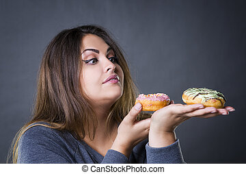 Beautiful young caucasian plus size model posing with donuts on a gray studio background