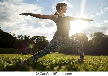 Beautiful young caucasian woman practices yoga asana Virabhadrasana 1