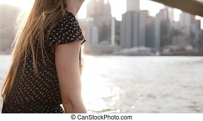 Beautiful young Caucasian woman sitting on embankment fence at Brooklyn Bridge, New York, enjoying view slow motion.